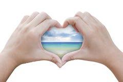 Händer i formen av hjärta med havet Arkivbilder