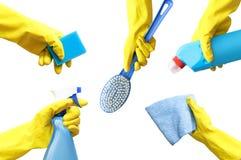 Händer i gula gummihandskar rymmer ett tvättmedel, en trasa, en flaska av sprej, en borste, en svamp för att göra ren isolaten arkivfoto