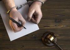 Händer i handbojor och en hammare av domaren royaltyfri fotografi