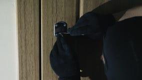 Händer i handskar som öppnar låset med dyrkar lager videofilmer