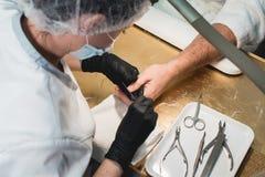 Händer i handskeomsorger om handen för man` s spikar Manikyrskönhetsalong Spikar arkiveringen med mappen royaltyfri foto