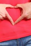 Händer i hjärta formar på buken, symbol av förälskelse Royaltyfria Bilder