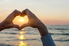 Händer i hjärtaform som inramar solen arkivfoton