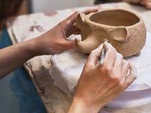 Händer i lera att göra en keramisk bunke arkivfoto