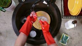 Händer i röda rubber handskar som tvättar ett exponeringsglas lager videofilmer