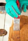 Händer i skyddande handskar som målar det wood brädet Arkivbild