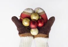 Händer i stack tumvanten med julbollar som isoleras på vit bakgrund Royaltyfri Fotografi