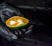 Händer i svarta handskar och i dem en cappuccino med lattekonst i avokado Ovanlig kopp Nytt och härligt kaffe med mjölkar arkivfoton