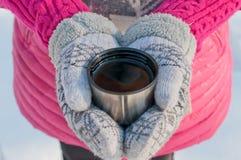 Händer i tumvanten rymmer en kopp från en termos med te Fotografering för Bildbyråer