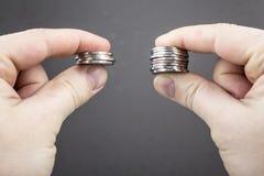 Händer jämför två högar av mynt av olika format royaltyfri bild