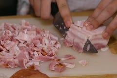 Händer klippte becon till små stycken för framställning av fyllning för pastasås Royaltyfria Bilder