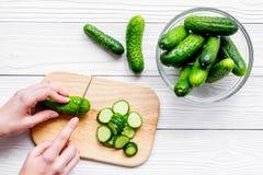Händer klippte nya gurkor på skärbräda Grå träcopyspace för bästa sikt för bakgrund Royaltyfri Foto