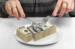 Händer klippte pengar på plattan, förminskar fondbegrepp Arkivbilder