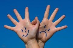 Händer länkade ihop med leenden och sorgsenhetmodellen Arkivbild