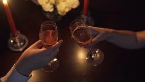 Händer man och en kvinna som klirrar exponeringsglas med champagne red steg framställning av ett förbindelseförslag stock video