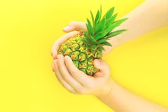Händer med ananas på gul bakgrund för sommarneon royaltyfri fotografi