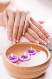Händer med aromatiska stearinljus och handduken. Spa Royaltyfri Foto