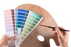 Händer med borsten, färgprövkopior och den tomma paletten arkivbilder