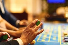 Händer med chiper på pokerrouletttabellen som spelar i en kasino royaltyfri foto