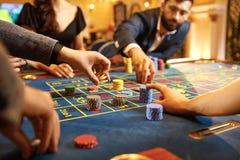 Händer med chiper på pokerrouletttabellen som spelar i en kasino arkivfoto