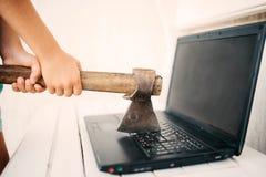 Händer med en yxa och en bärbar dator fotografering för bildbyråer