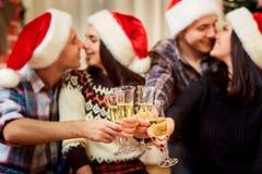 Händer med exponeringsglas av champagne på bakgrunden av den kyssande couen Arkivbilder