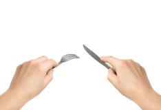 Händer med kniven och gaffeln Arkivfoto