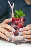 Händer med manicured kort spikar kulört med grå färger spikar polermedel royaltyfri foto