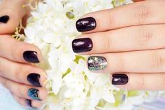 Händer med manicured spikar kulört med mörka lilor spikar polermedel arkivfoto
