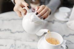 Händer med manikyr häller teet in i koppen Royaltyfri Bild