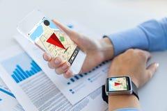Händer med navigatöröversikten på den smarta telefonen och klockan Royaltyfria Foton