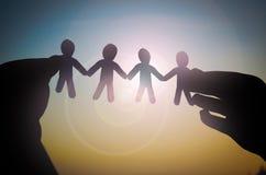 Händer med pappers- människakontur på solen Royaltyfri Bild