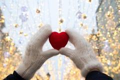 Händer med röd hjärta på snön royaltyfri bild