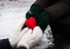 Händer med röd hjärta på snön royaltyfria bilder
