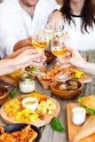 Händer med rött vin som rostar över den tjänade som tabellen med mat Royaltyfria Bilder