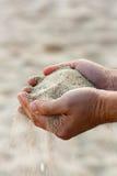 Händer med sand Arkivbild