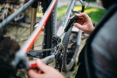 Händer med skruvmejselreparationsskiftaren, cykelreparation arkivfoton