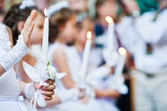 Händer med stearinljus av små flickor på den första heliga nattvardsgången Royaltyfri Fotografi