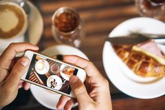 Händer med telefonen Frukost för två: en giffel med skinka, kaffe, en uppfriskande drink Royaltyfri Foto