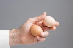 Händer med två hönaägg arkivfoto