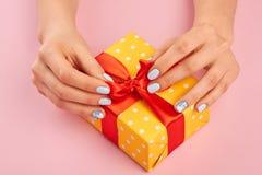 Händer med vintermanikyr som packar upp gåva Royaltyfri Fotografi