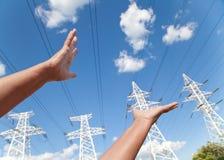 Händer når för maktöverföringslinjer mot blå himmel Royaltyfri Foto