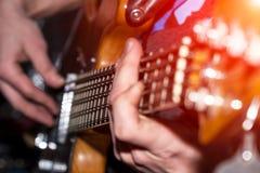 Händer och fingrar av basen för gitarrist` s på fretboarden arkivbild