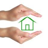 Händer och grönt hus royaltyfri fotografi
