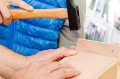Händer och hammare Arkivfoton