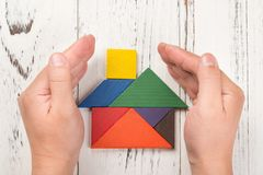 Händer omger ett trähus som göras av begrepp för tangramhemförsäkring Arkivfoton