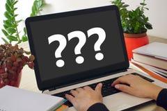 Händer på bärbar datortangentbord- och frågefläckar på bärbar datorskärmen Arkivfoto