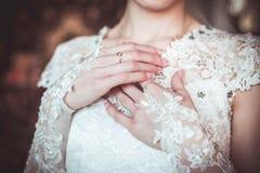 Händer på bröllopsklänningen Arkivbilder
