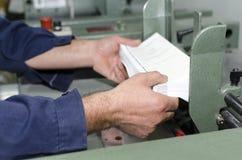 Händer på den fulländande linjen maskin för stolpepress arkivbilder