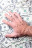 Händer på dollarbills Royaltyfri Foto